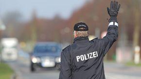 Ein Polizist hebt seinen Arm, um ein Auto anzuhalten