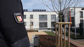 Außenansicht der JA Schleswig, im Vordergrund ein Justizbeamter