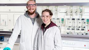 Ein junger Mann und eine junge Frau mit weißen Kitteln und Schutzbrillen stehen in einem Labor.