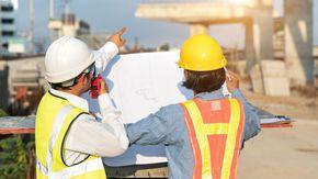 Zwei Männer stehen mit einem Bauplan vor einer Brückenbaustelle