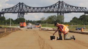 Ein Arbeiter baut eine Straße. Im Hintergrund sieht man die Eisenbahnbrücke von Rendsburg.