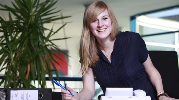 Eine junge Frau an ihrem Arbeitsplatz im Büro.