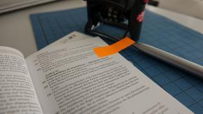 Ein Grundgesetz liegt aufgeschlagen auf einer Aktenmappe, daneben liegen ein Stempel und ein Stift.