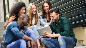 Ein Gruppe junger Menschen (drei Frauen und zwei Männer sitzen zusammen auf einer Treppe und schauen auf ein Tablet.