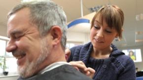 Eine Friseurin schneidet einem älteren Herren die Haare.