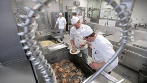 Mehrere Köche und Küchenhelfer arbeiten in einer Großküche
