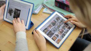 Zwei Schulkinder benutzen im Unterricht ein Tablet