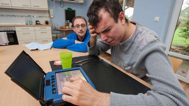 Ein Schüler sitzt neben seinem Lehrer am PC.