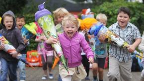 Fröhliche Kinder mit Schultüten laufen auf die Kamera zu