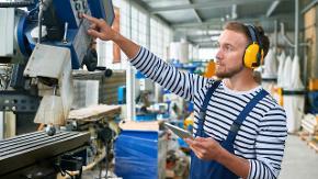 Ein Mann steht an einer Industriemaschine und hält ein Tablet in der Hand.