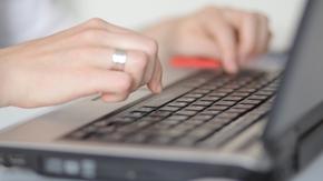 Hände tippen auf der Tastatur eines Notebooks