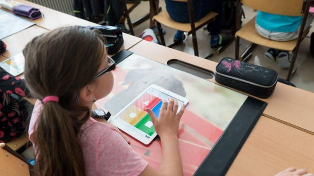 Eine Grundschülerin sitzt an ihrem Pult, vor ihr liegt ein iPad.