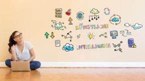 Eine junge Frau sitzt vor einer Wand mit bunten Symbolen. In bunten Buchstaben sind die Worte Künstliche Intelligenz an die Wand geschrieben.