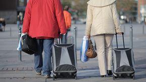 Zwei Menschen ziehen Koffer hinter sich her.