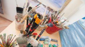 Mehrere Pinsel stehen in Gläsern auf einem Tisch