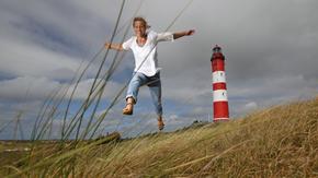 Eine Frau läuft fröhlich durch die Dünen, im Hintergrund der Leuchtturm von Amrum
