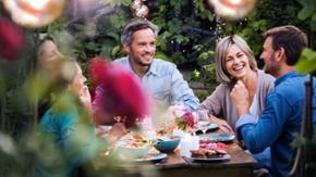 Mehre Menschen sitzen im Garten um einen Tisch herum