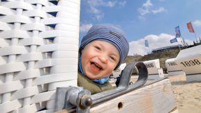 Ein kleiner Junge lacht aus einem Strandkorb heraus in die Kamera.