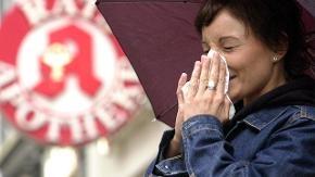 Eine Frau steht vor einer Apotheke und niest in ein Taschentuch.