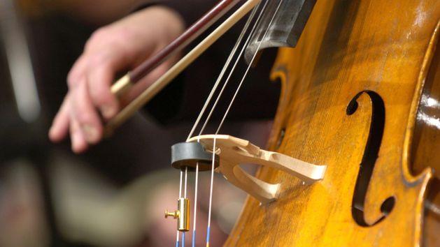 Nahaufnahme eines Cellos und einer Hand, die den Bogen hält
