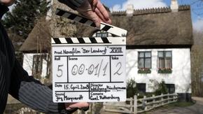 """Filmklappe zu Dreharbeiten """"Der Landarzt"""" vor Reetdachhaus"""