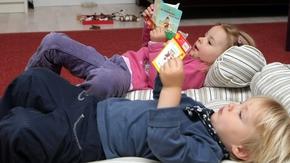 Zwei Kindergartenkinder schauen sich Pixibücher an