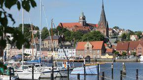 Blick auf das Stadtpanorama von Flensburg. Im Vordergrund sind Segelboote zu sehen, im Hintergrund historische Gebäude.
