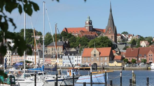 Eine Ansicht der Flensburger Nordstadt vom Ostufer der Förde. Im Vordergrund liegen Segelboote.
