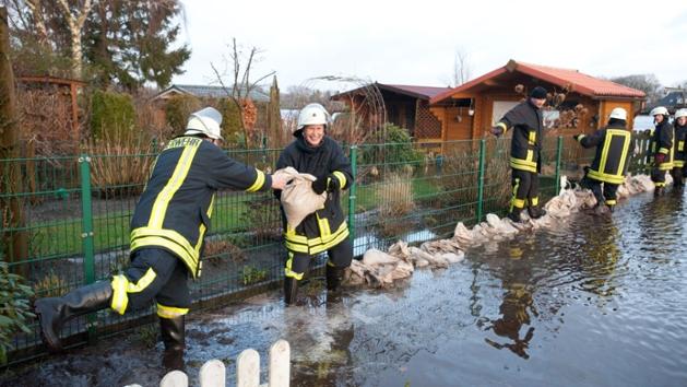Sechs Feuerwehrleute schützen einen Kleingarten mit einem Sandsackwall vor der Überflutung