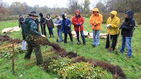Ein Forstwirt erklärt einer Gruppe von Menschen verschiedene Baumarten