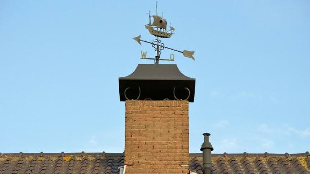Ein Schornstein mit einer Wetterfahne auf einem Dach