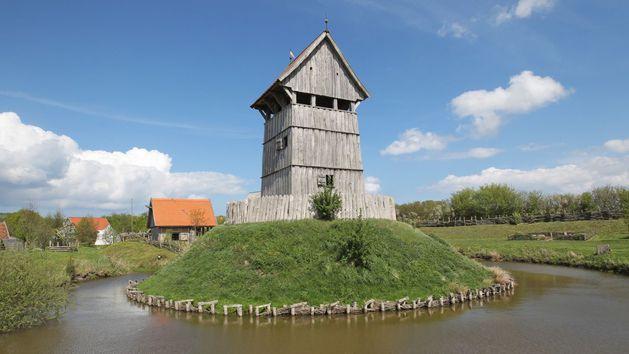 Ein hölzerner Turm steht auf einer kleinen Insel umringt von Wasser. Im Hintergrund stehen einige Gebäude.