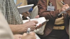 Nahaufnahme mehrerer Hände, die mit Kugelschreiber und Block Notizen machen