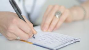 Nahaufnahme von Frauenhänden, die Notizen auf einem Spiralblock machen