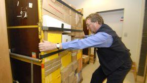 Ein Postmitarbeiter räumt Pakete in ein Regal