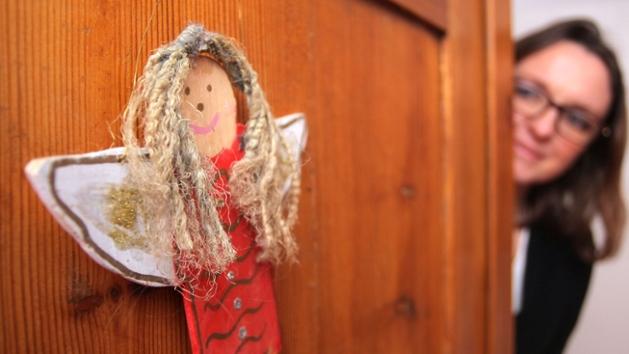 Eine Frau öffnet eine Haustür. An der Tür hängt eine kleine Engelsfigur.