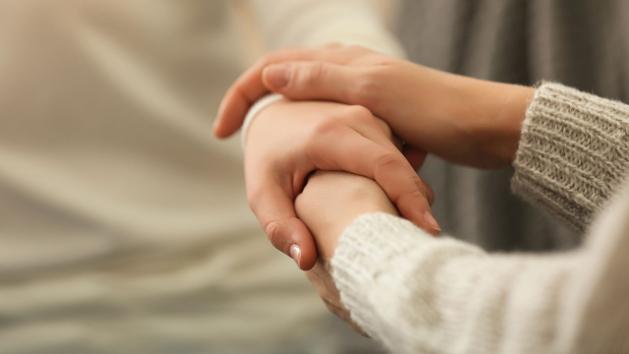 Zwei Hände halten tröstend eine dritte Hand.