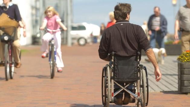 Ein Rollstuhlfahrer in einer Fußgängerzone