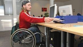 Ein Mann im Rollstuhl macht Büroarbeit in einer Behörde