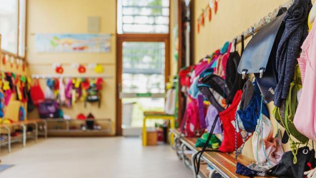 Viele Jacken und Rucksäcke hängen an den Wänden in einem Raum.