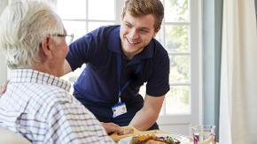 Ein Pfleger bringt einem älteren Mann etwas zu essen.