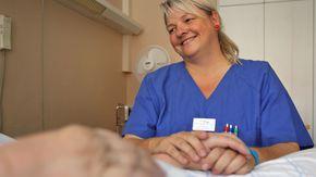 Eine Krankenschwester hält lächelnd die Hand eines Patienten.