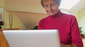 Eine ältere Frau sitzt vor einem Laptop.