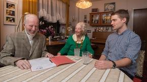 Senioren sitzen mit einem Studenten zusammen am Tisch