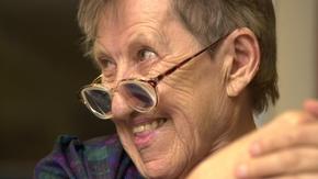 Porträt einer Seniorin, die lächelnd über den Rand ihrer Brille schaut