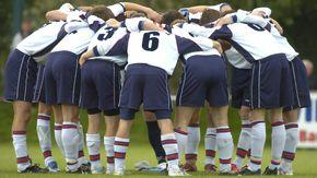 Eine Fußballmannschaft bildet einen Kreis, um sich auf das bevorstehende Spiel einzuschwören.
