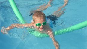 Ein Junge mit Schwimmbrille lernt mit Hilfe einer Poolnudel schwimmen.