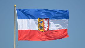 Die Schleswig-Holstein-Flagge weht im Wind
