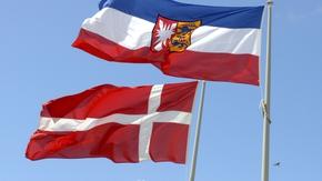 Vor blauem Himmel wehen die Flaggen von Schleswig-Holstein und Dänemark