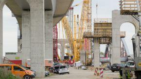 Im Bild sieht man eine große Baustelle: Links und rechts finden sich Brückenteile, in der Mitte zahlreiche Maschinen.